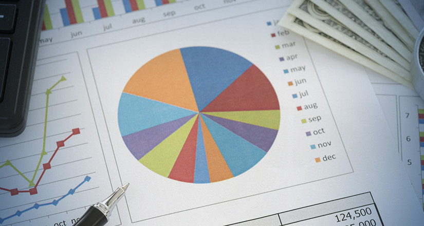 Pen on Pie chart and graphs business report with money, compass, calculator on desk of financial advisor.  Accounting and Financial Planning Concept