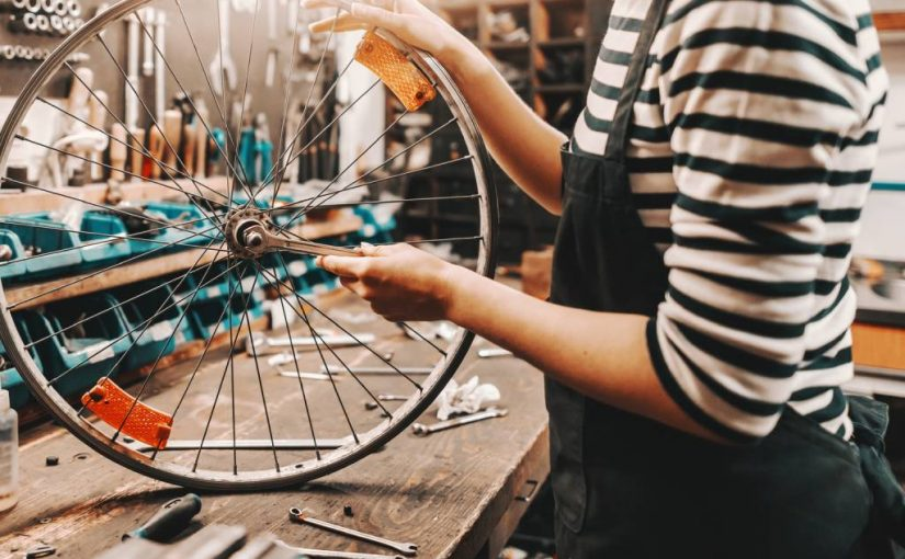 female worker holding and repairing bicycle wheel while standing in bicycle workshop