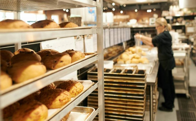 rack of freshly baked goods with a woman working in the background at a bakery