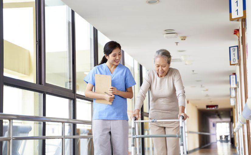 Senior walking in nursing home with nurse